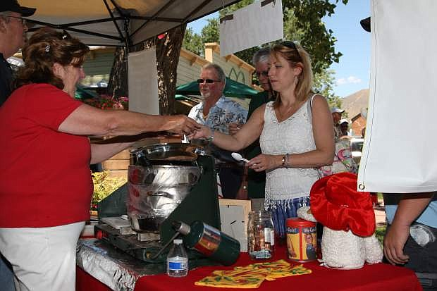 Terri Mellon of Reno takes a sample from Dione Cooley of 'Reno's Red Hot Mama' chili on Saturday at Glen Eagles.