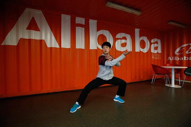 In this photo taken Tuesday March 26, 2013 and made available March 11, 2014, a worker performs shadow boxing during an open day at the Alibaba Group office in Hangzhou in east China's Zhejiang province. Ten companies including Internet giants Alibaba and Tencent have been picked to invest in China's first five privately owned banks, the industry's chief regulator said Tuesday, March 11, 2014. (AP Photo) CHINA OUT