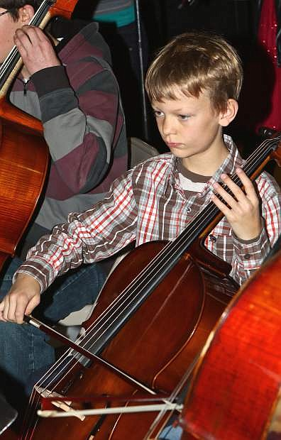 Halen Harrison, 9, plays his Cello at the Christmas Carol String Playalong Friday at the Carson Mall. This was the event's sixth year.