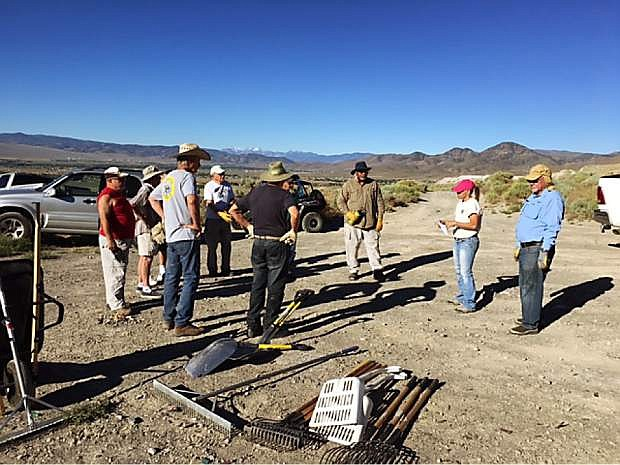 Cleanup starts on a BLM Adopt-A-Site near Basalite Quarry east of Dayton with BLM Program Coordinator Corey Gardner, in the pink hat, who holds a safety meeting with residents of Copper Canyon Estates.
