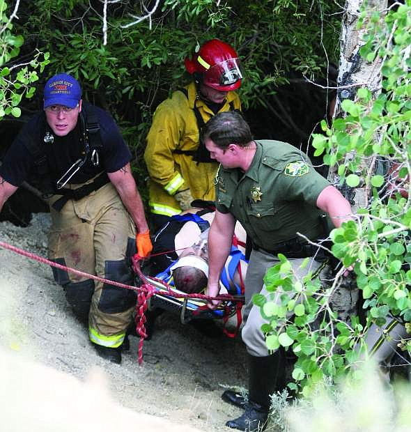 Carson City sheriff's deputies, firefighters and paramedics carry a man up an embankment near Clear Creek Road on Friday evening after he fell while rock climbing.