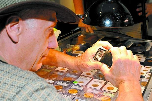 Published Caption: John Shott of South Lake Tahoe uses a magnifying glass to inspect a coin on Saturday at the coin show at the Nevada State Museum.