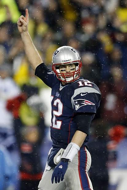 New England Patriots quarterback Tom Brady celebrates running back Stevan Ridley's touchdown during the second half of an AFC divisional NFL playoff football game against the Indianapolis Colts in Foxborough, Mass., Saturday, Jan. 11, 2014. (AP Photo/Michael Dwyer)