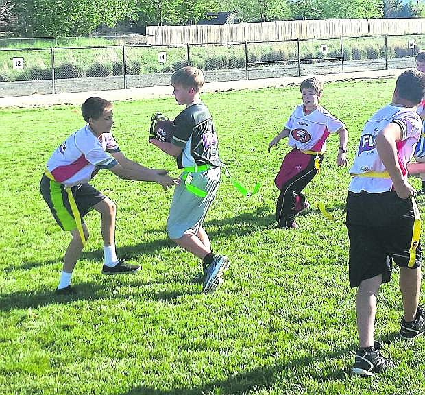 Trevor Marlin of the 49ers pulls the flag of the Saint, Alex Myrehn running while, Braden Rice, top right, and Kory Grist, bottom right, are in pursuit during recent Carson City NFL flag football action.
