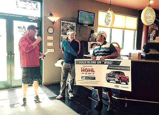 On Saturday, Jason Clark made a hole-in-one on the 14th hole during the American for Wounded Veterans tournament at Silver Oak Golf Course in Carson City. Clark won a brand new 2015 Chevy Silverado Crew Cab 4x4 from Michael Hohl Motor Company of Carson City. Making the presentation in the club house is Michael Hohl Motor Company General Sales Manager, Gary Gamba, left, with head golf pro Robert Mason, center, looking on. Jason and Jenna visited the dealership on Monday to decide which color of truck they would like to take home.
