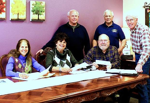 Barbara Slade, Debbie Posnien and Dave Nelson, seated, work with Kiwanis members John Cole, Rudy Hammond, and Peter Engle on the club's Feb. 22 benefit concert by Woody and the Longboards at the CVIC Hall in Minden.