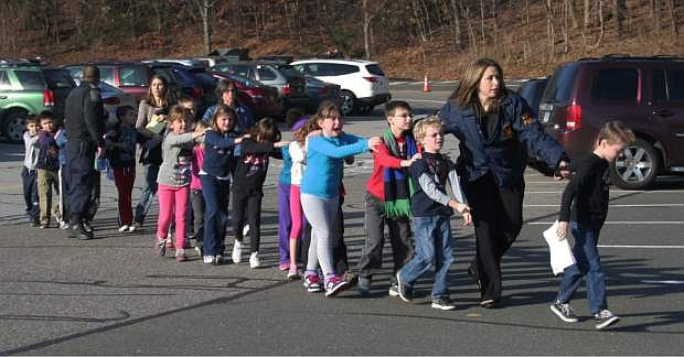 FILE - In this photo provided by the Newtown Bee, Connecticut State Police lead a line of children from the Sandy Hook Elementary School in Newtown, Conn. on Friday, Dec. 14, 2012 after a shooting at the school.  Recordings of 911 calls from the Newtown school shooting are being released Wednesday Dec. 4, 2013, days after a state prosecutor dropped his fight to continue withholding them despite an order to provide them to The Associated Press. (AP Photo/Newtown Bee, Shannon Hicks, File) MANDATORY CREDIT: NEWTOWN BEE, SHANNON HICKS