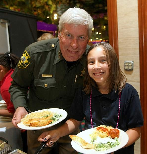 Carson City Undersheriff Steve Albertsen and 10-year-old Alexia Bourcier share a smile and fill their plates at the Cops and Kids Spaghetti Dinner on Tuesday.