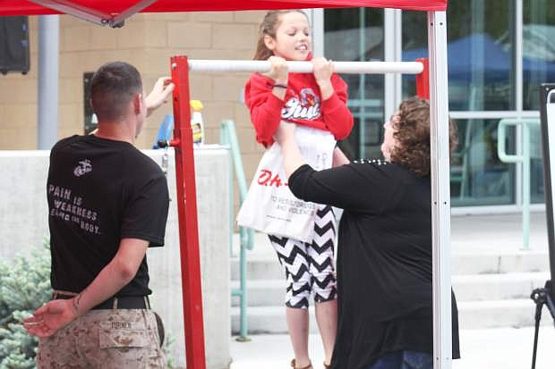 A Cops and Kids attendee tries to do a pull up at the Marine tent Saturday. The Marines were there to promote their organization at the event and interact with the community.