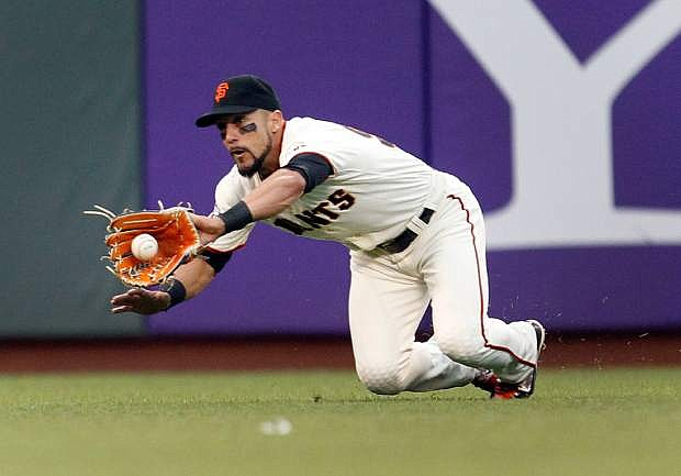 San Francisco Giants left fielder Andres Torres makes a diving catch on a hit by Chicago Cubs' Nate Schierholtz during the sixth inning of a baseball game on Saturday, July 27, 2013, in San Francisco. (AP Photo/Tony Avelar)