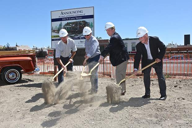 Hop and Mae Adams Foundation trustees Chris MacKenzie, Steve Neighbors and Ed Ahrens along with Mayor Bob Crowell (3rd from left) scoop dirt at 308 N. Curry Wednesday for the groundbreaking of the new multi-use complex.
