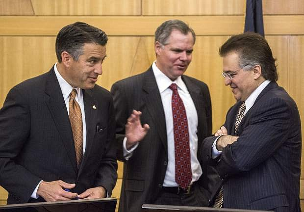 """FILE - In this May 13, 2016, file photo, Nevada Gov. Brian Sandoval, left, Bill Murren, CEO of MGM Resorts International, and Tony Alamo, chairman of Nevada Gaming Commission, talk during the Gaming Policy Committee meeting to discuss """"esports"""" in Las Vegas. Daily fantasy sports websites are trying to get legal after a series of state-level setbacks that shut them down in some parts of the country, but decision-makers in the gambling mecca of Nevada indicated they won't be bending too far backward for the companies. (Jeff Scheid/Las Vegas Review-Journal via AP, File)"""