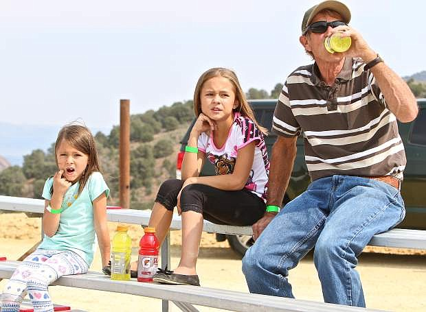 Emma Forest-Crawford, 6, of Reno and her 9-year-old sister Sopia take in the camel racing with their grandfather Michael Crawford of Myrtle Creek, Or. in Virginia City Friday.