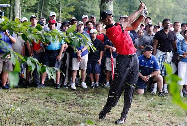 Tiger Woods hits out of the rough on the 12th hole during the final round of the Deutsche Bank Championship golf tournament in Norton, Mass., Monday, Sept. 2, 2013. (AP Photo/Michael Dwyer)