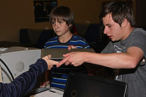 Samuel Johnson, 14, and Donovan Warner, 15, check out Apple laptops at the newly re-opened Digitorium at the Carson City Library Thursday afternoon.