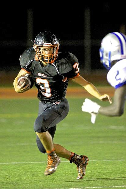Tigers runningback Sam Melhus carries the ball for a gain against McQueen Friday night at Keith Roman Field.