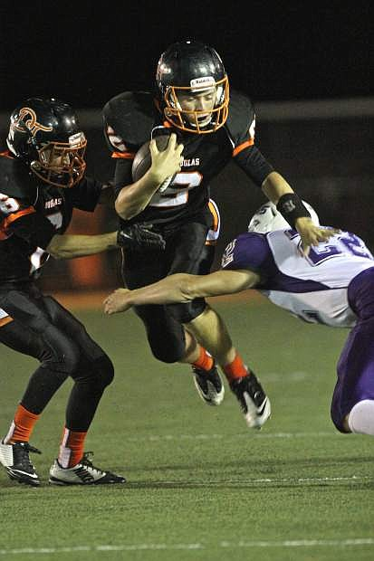 Douglas quarterback Bryce James leaps past a Spanish Springs defender Friday night at Douglas High. The Tigers won the game 23-13.
