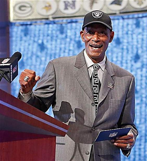 Former Oakland Raiders cornerback Willie Brown reacts as he announces Fresno State quarterback Derek Carr as the 36th pick by the Oakland Raiders in the second round of the 2014 NFL Draft, Friday, May 9, 2014, in New York. (AP Photo/Jason DeCrow)