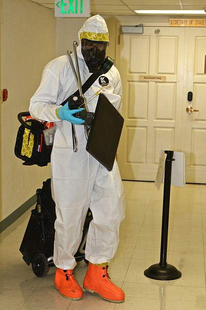 Staff Sergeant Richard Jager is seen in a hazmat suit bringing monitoring equipment into the basement of the State Capitol Wednesday morning during a 92nd Civil Support Team drill.