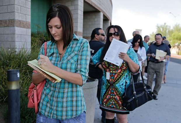 Waiting for doors to open, Las Vegas and Henderson, Nev. residents line up outside the Department of Motor Vehicles to renew vehicle registration and drivers licenses, Wednesday, Aug. 7, 2013, in Henderson, Nev. The Nevada state Department of Motor Vehicles is working on rules to determine what kind of residency paperwork will be accepted from tens of thousands of people who are expected to seek state driver privilege cards for the first time after Jan. 1. The state Legislature passed a law this year putting Nevada among several states letting people who don't have legal U.S. residency obtain driver authorization cards. (AP Photo/Julie Jacobson)