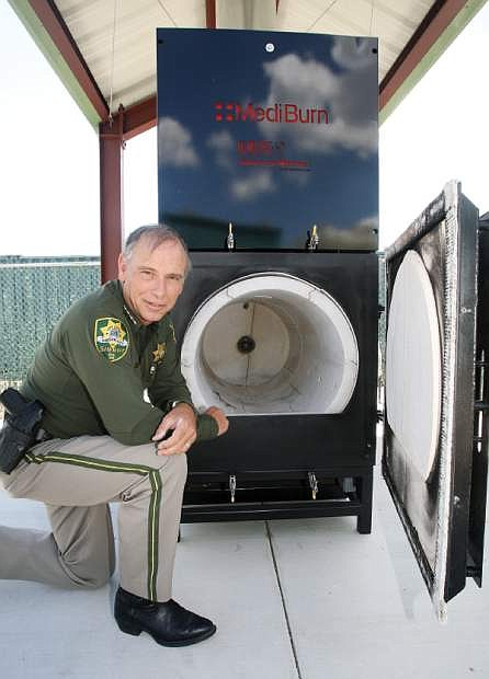 Carson City Sheriff Ken Furlong kneels next to a dual-chamber burner that will be used to incinerate contraband.