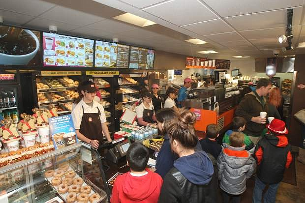 Customers order donuts and coffee during the grand opening of Dunkin' Donuts on Tuesday morning.