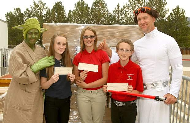 """Eagle Valley Middle School principal Lee """"Princess Leia"""" Conley and vice-principal Dr. Susan """"Yoda"""" Moulden congratulate students, from left, April Tedrowe, Anika Soulier and Jeremy Parman for raising the most money for the school's annual cookie dough fundraising event."""