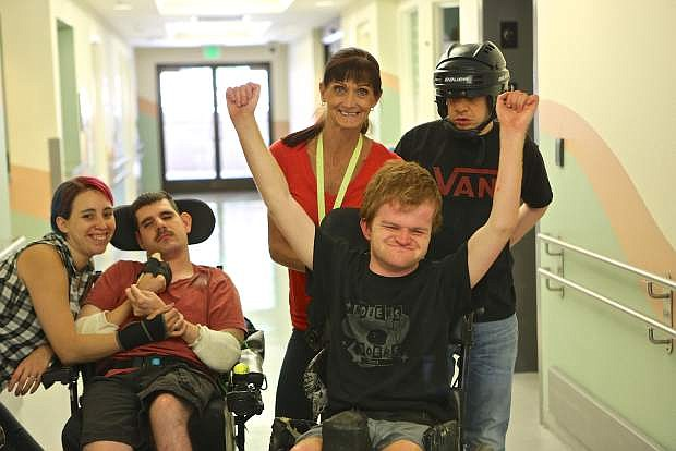 Direct Care Trainers Teresa Gonzales (left) and Noreen Fish (center) pose for a photo with Eagle Valley clients Brandon, Justin and Todd.