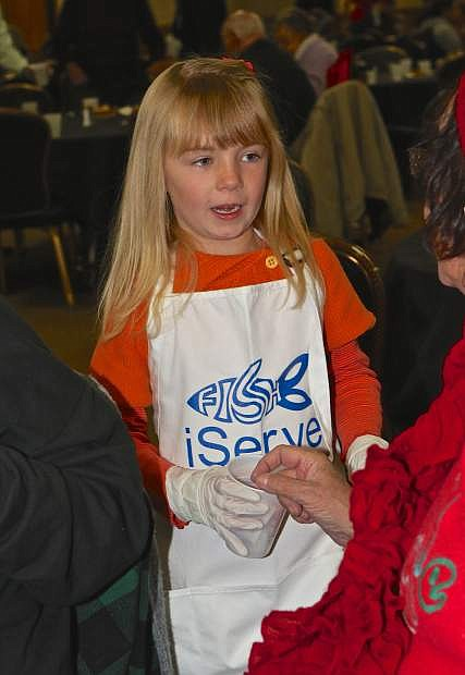Six-year-old volunteer Bree Griffin gives a Thanksgiving Day dinner attendee some sugar for her coffee Thursday at the Carson Nugget.