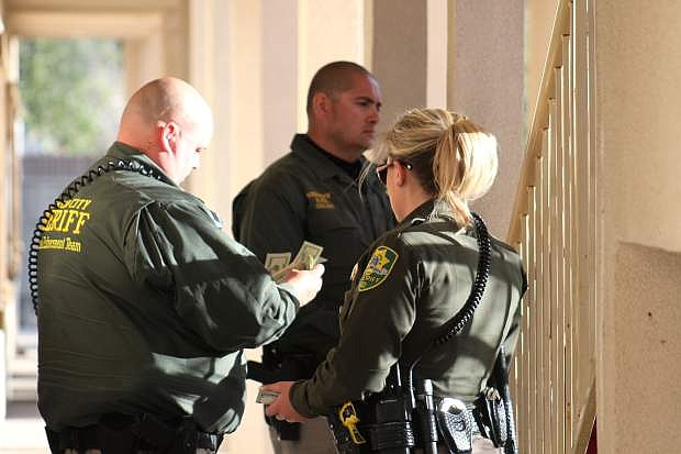Members of the Carson City Sheriff's Office Special Enforcement Team count money Friday night after arresting a man who had previously agreed to be a confidential informant.