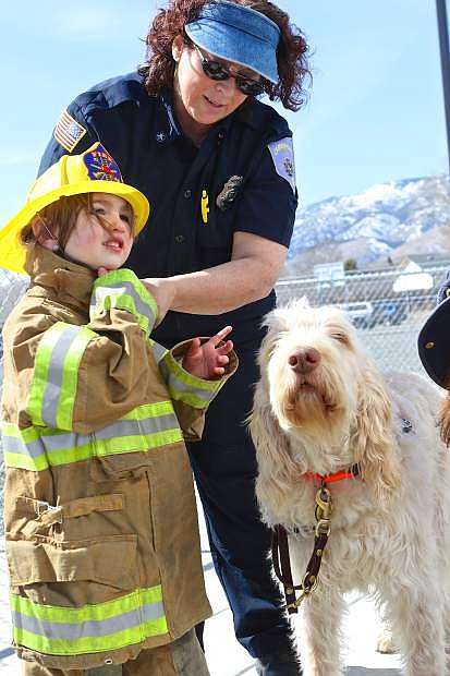 Kenzee Alvarez, 3, receives assistance in getting her turnouts on from Carson City Fire Department's Lee Horton and the department's fire dog, Tizzy, Saturday at the Boys and Girls Clubs during the first annual Early Childhood Expo.
