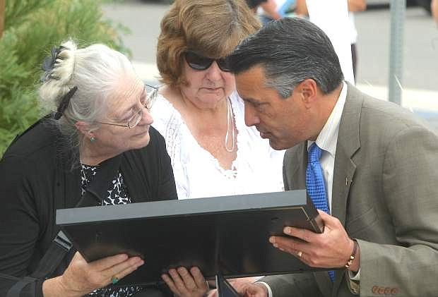 Gov. Brian Sandoval presents a State Flag and Proclamation to Susan Arding during the Nevada Department of Transportation Memorial Star Dedication to her son Ron Raiche, Jr. on Monday.
