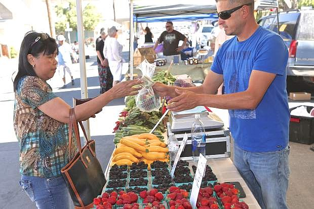 Zeny Logan (left) purchases some blackberries from RHJ Organic's Rafael Garcia at a new farmer's market Wednesday evening on Curry Street. The market is being launched by Doug Cramer, owner, Mom & Pops Diner, and operated by Lake Tahoe Markets.