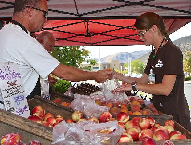 CNA/EKG Tech Cassandra Aveiro purchases fresh peaches from Erik Kisbye of R. Schletewitz Family Farms of Sanger, Calif. at the farmer's market Thursday at Carson-Tahoe Medical Center.