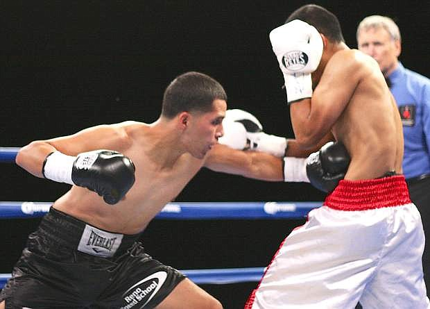 Reno's Oscar Vasquez, left, lands a body blow to Sergio Lopez of Las Vegas during Friday's Fallon Fights at the Churchill County Fairgrounds.