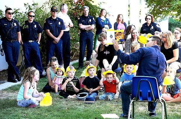 """Youth Services Librarian Matt Galli, right, reads at the Carson City Library Storytime on Thursday, July 24, 2014. The Carson City Fire Department joined the library for the launch of their """"Fire Safety Day"""" children's book. The free book, which is also available as an e-book, is available during business hours at the main fire station at 777 S. Stewart St."""