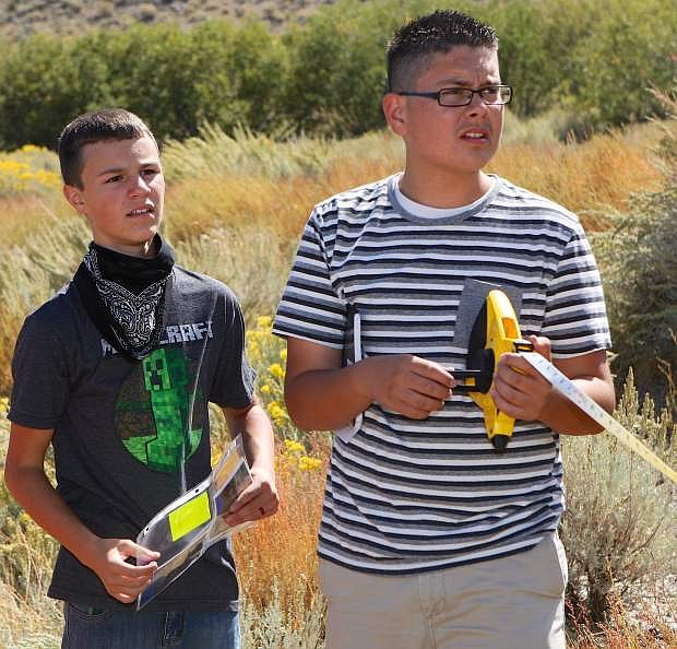 Freshmen biology students Adam Daniels, left, and Edson Lemus make some measurements in the area of the Waterfall Fire Thursday.