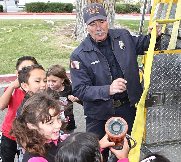 Carson City firefighter Perry Carlson shows first graders from Ms. Smith's and Ms. Short's class how heavy a firehose is on Wednesday at Mark Twain Elementary.
