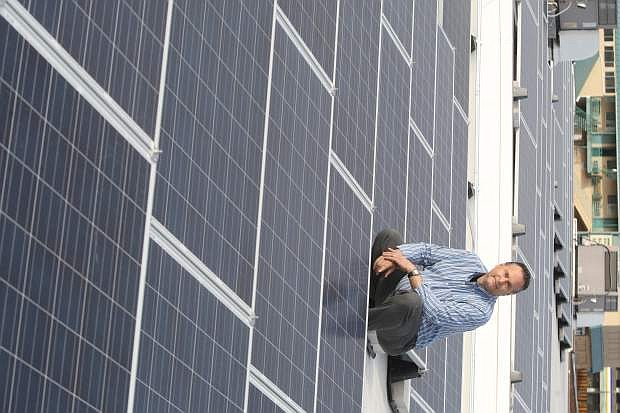 FISH executive director Jim Peckam kneels next to the solar panels installed on the roof of the FISH thrift store and dining halll. The 130 solar panels can generate 28 kilowatts of power.