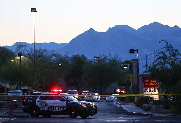 In this photo taken Wednesday, June 29, 2016, Las Vegas police investigate a homicide outside of a Walgreens at Lake Mead and Jones Boulevards in Las Vegas. A man chased and gunned down his wife outside the drug store and killed their three children at an apartment in Las Vegas before apparently shooting himself, leaving five members of a family dead, authorities said Thursday, June 30, 2016.  (Chase Stevens/Las Vegas Review-Journal via AP)