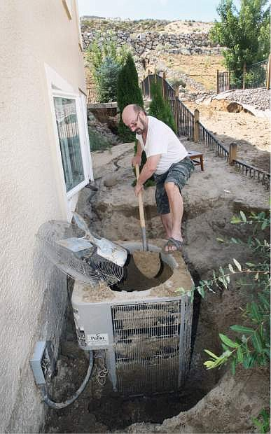 Roman Friedman, who lives on Long Drive in Sunridge digs out his air conditioner on Monday after it was buried in nearly five feet of sand that washed down the hillside behind his home during Sunday's severe thunderstorm,