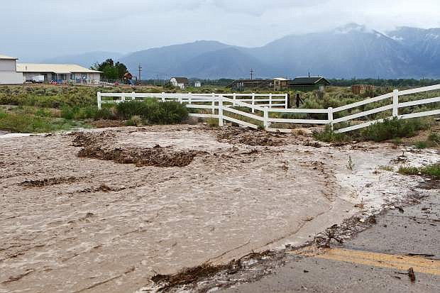 Flash flood waters pour across East Valley Rd. just north of Pinenut Rd. in south Gardnerville Wednesday afternoon after the Pinenut Range to the east received heavy rain from remnants of tropical storm Blanca. Further east, Yerington reported 2 inches of rain in 20 minutes.