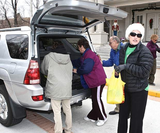 """Starbucks employee Christina Krische (holding bag) volunteers at the """"Share Your Christmas"""" food drive at the Governor's Mansion while Erica Steele, left, helps food donator Josie Leeds, center, of Dayton. The food drive also took place in Reno and at the Carson Valley Inn. The local drive benefitted Advocates to End Domestic Violence, FISH, and Ron Wood Family Resource Center."""