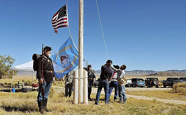 Re-enactors, members of the Nevada National Guard and Western Shoshone tribe raise an American flag and Western Shoshone flag Saturday during the opening of the interpretive trail at the fort at Fort Ruby.