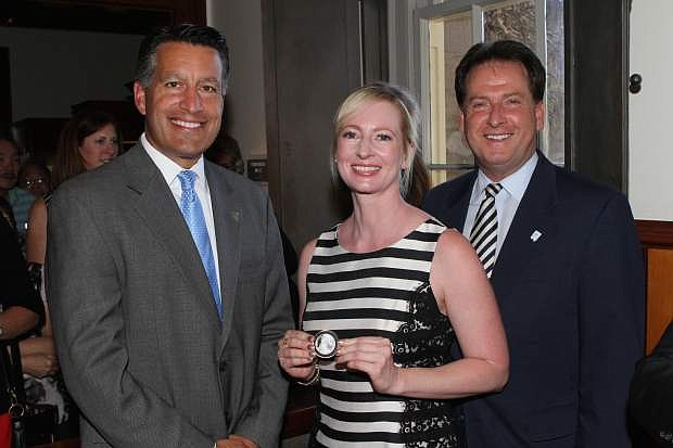 Drawing winner Danielle McVickers of Reno, center, poses with her freshly minted coin along with Gov. Brian Sandoval, left, and Lt. Gov. Brian Krolicki, right, at the Nevada State Museum Wednesday.