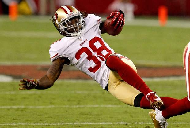 FILE - In this Oct. 29, 2012, file photo, San Francisco 49ers free safety Dashon Goldson is tackled against the Arizona Cardinals during the first half of an NFL football game in Glendale, Ariz.  All 32 teams are under the $123 million salary cap, but how much teams want to wheel and deal is unclear. Those available include Goldson, Ed Reed and Wes Welker.  (AP Photo/Ross D. Franklin, File)