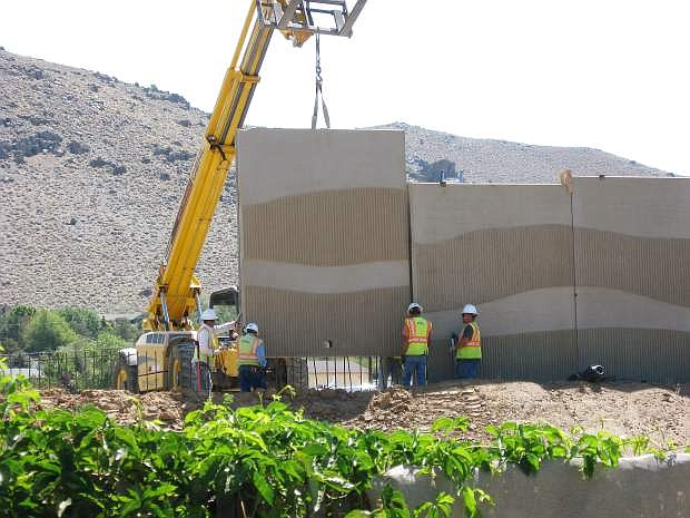 David Knighton submitted this photo of the sound wall going up along the Carson City Bypass. After the panels are lifted off a flatbed trailer, they are transferred to a forklift with a sling attachment and that equipment takes them to the wall where they are guided into place by the crew.
