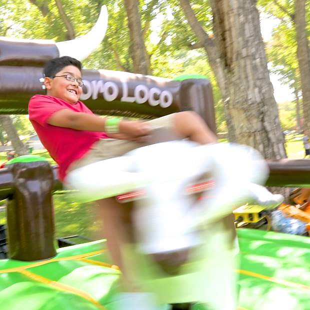 Leonardo Garcia, 10, takes a spin on the Toro Loco machine at the Northern Nevada Family Fun Day at Mills Park Saturday afternoon.