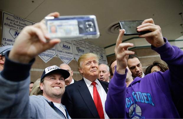 Republican presidential candidate Donald Trump, middle, takes a picture with supporters at a caucus site, Tuesday, Feb. 23, 2016, in Las Vegas. (AP Photo/Jae C. Hong)