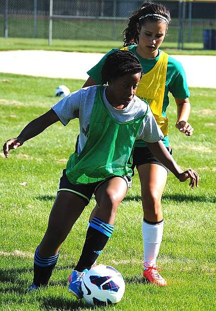 Lady Wave soccer player Erica Loyden, front, battles Britney Wallace for the ball during practice.